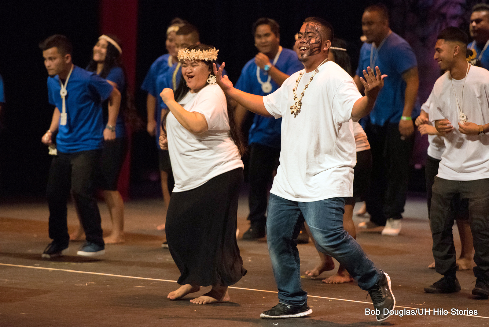 In background is group of women and men in blue shirts and black pants. In front is couple with white shirts dancing, man has arms extended out, woman is smiling with hand gesturing toward herself. He has a tattoo on his face, she has shell or flower head ornaments.