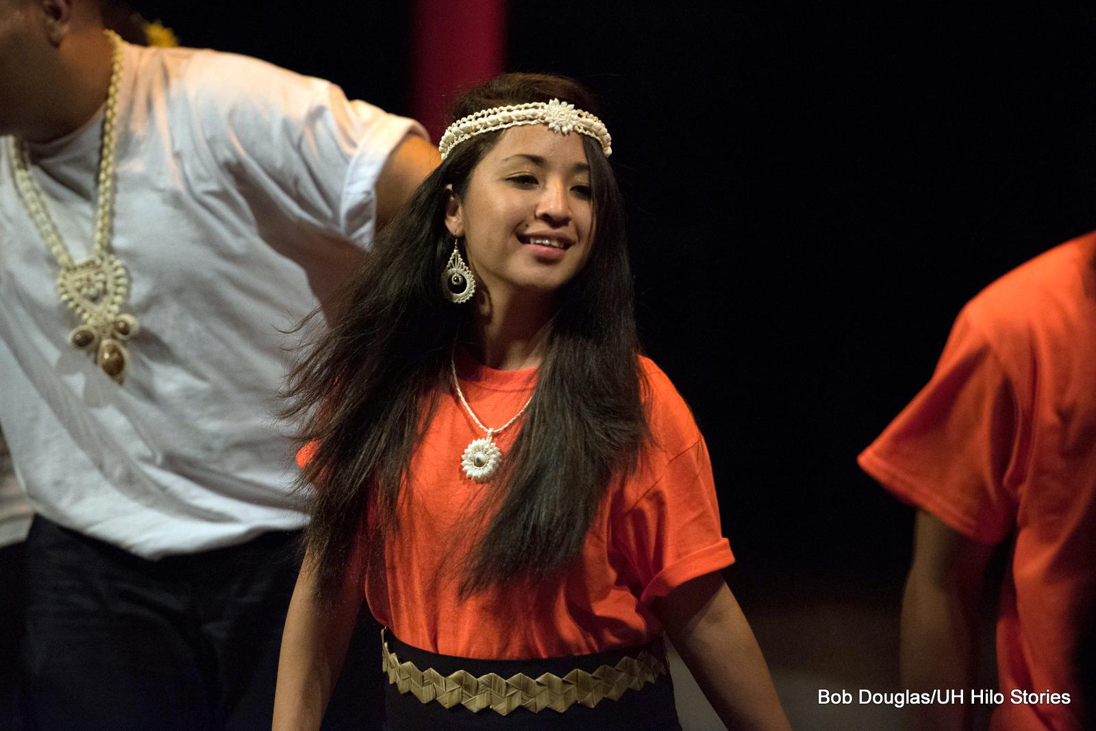 Woman in orange, dancing.