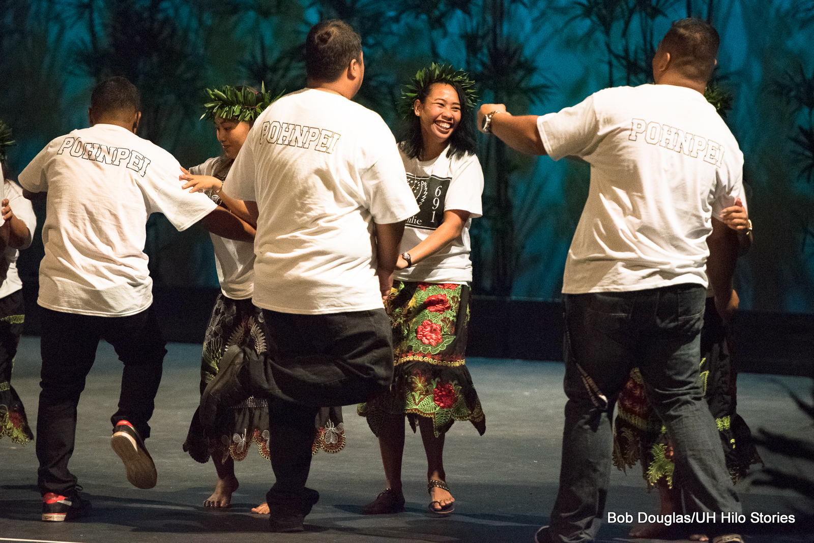 Dancers in pairs, women with colorful skirts and green leaf headdresses, one woman with big smile.