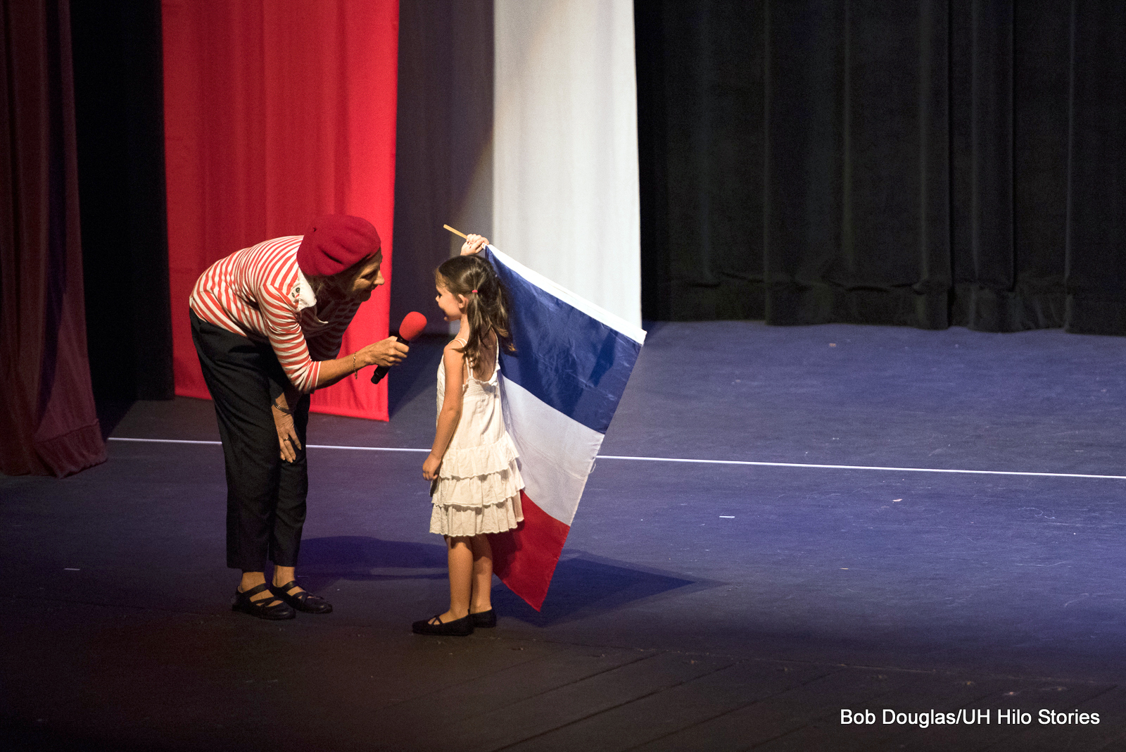 Woman holing microphone for young girl with flag.