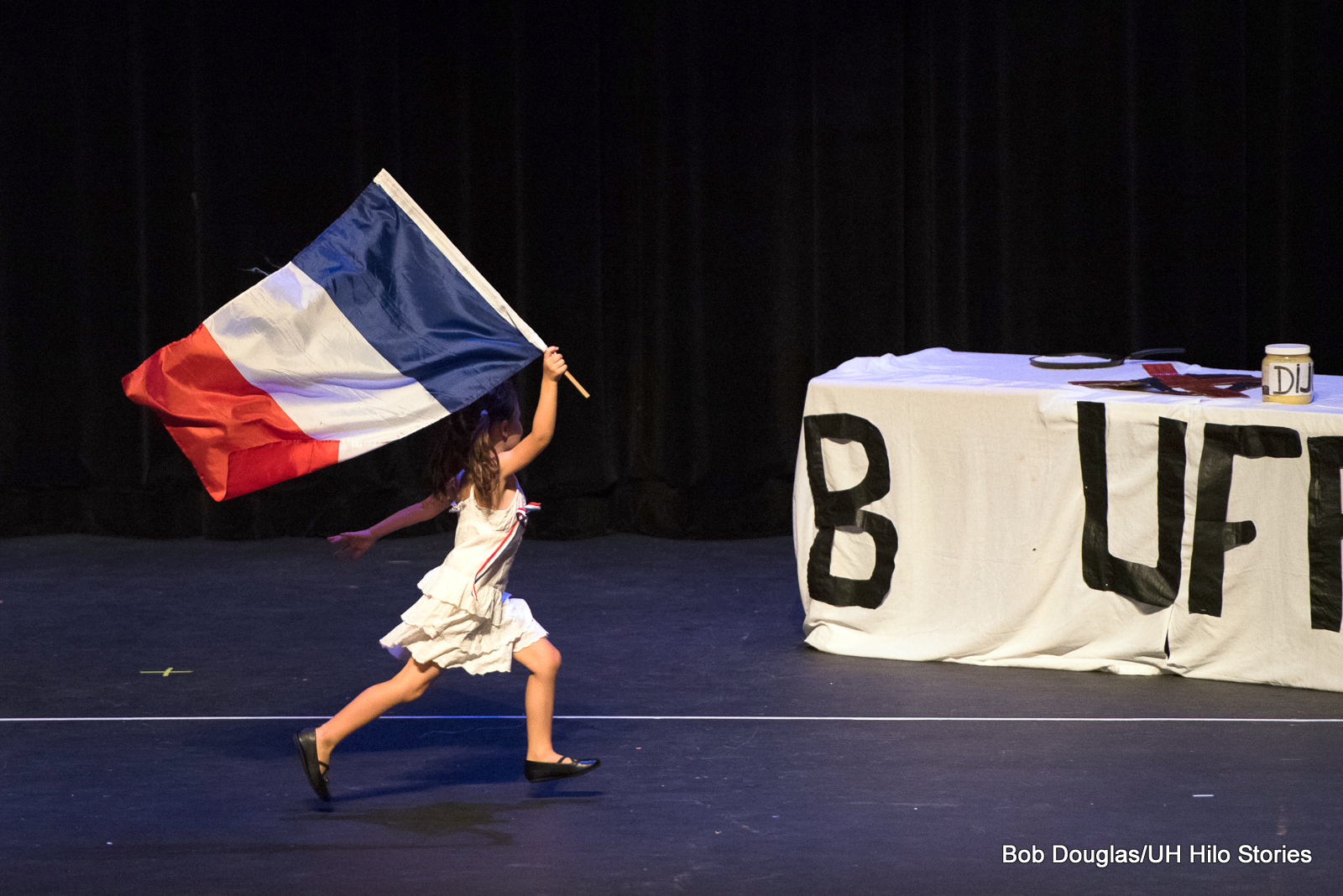 Young girl running across stage with the flag of France.