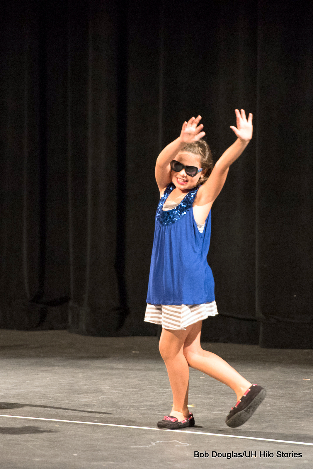 Girl in sunglasses, dancing, arms up.