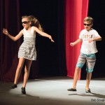 Boy and girl in shorts and sunglasses, dancing.