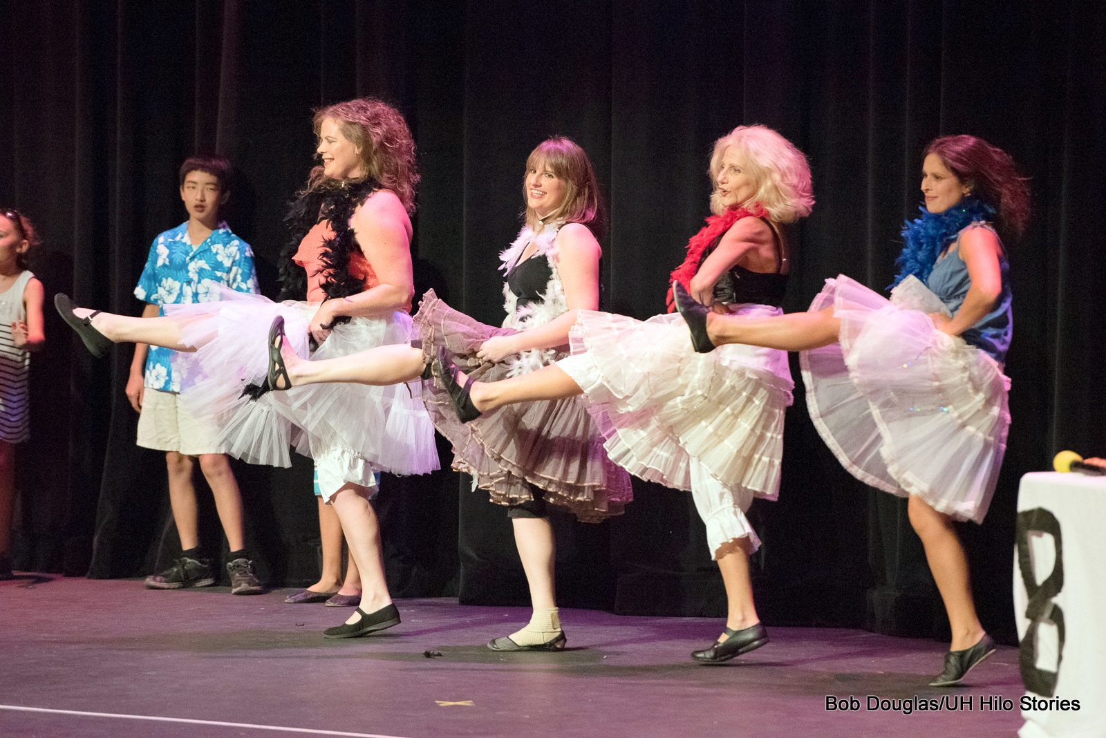 """Four women in white skirts doing a """"can-can"""" type dance, in line with left legs kicking up."""