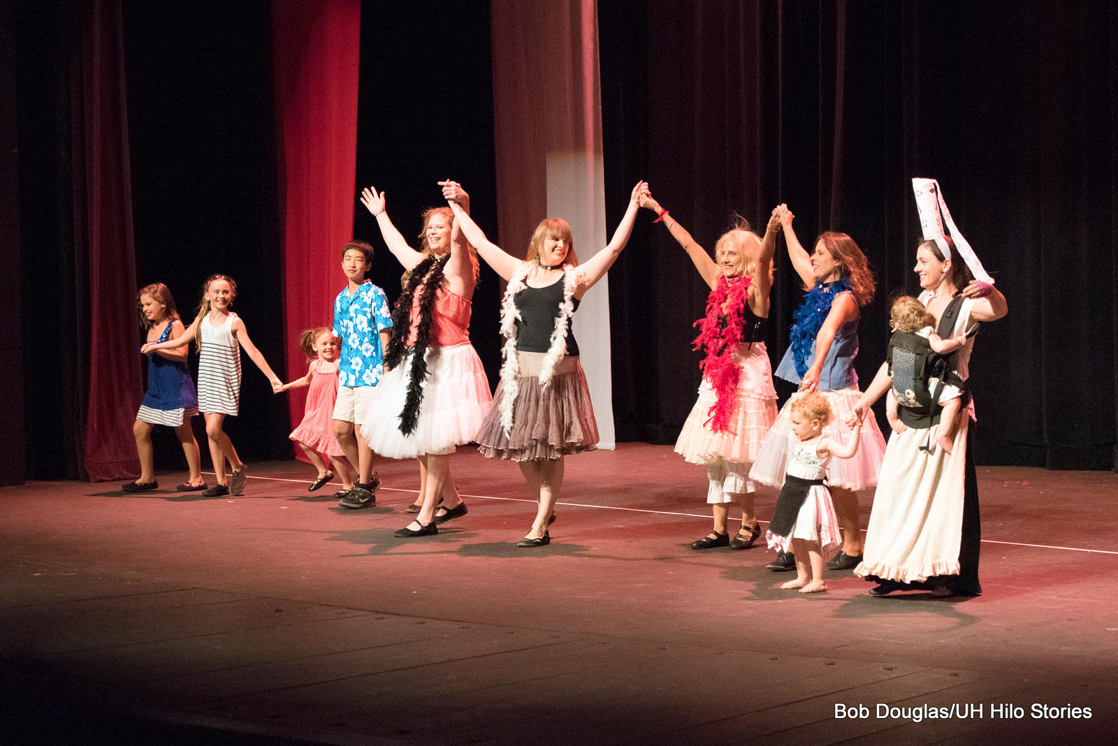 Girls raising arms together for final bow after performance.