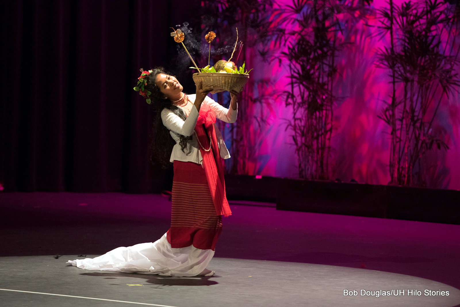 Single woman walking forward on stage, red and white costume, she is holding up basket of fruit with burning incense.