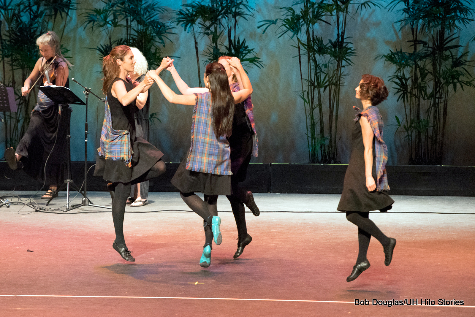 Four women dancing together, knees lifted.