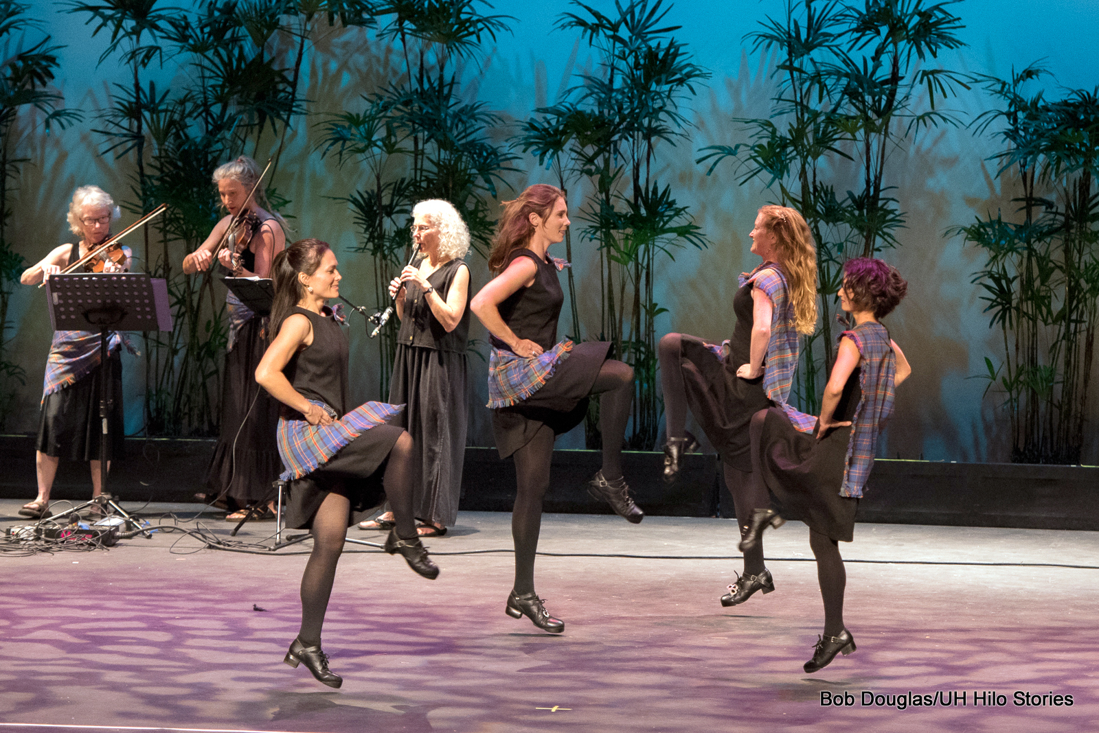 Four women in line, hands on hips, kicking up right feet swung left to other side. In background is quartet with keyboard and strings.