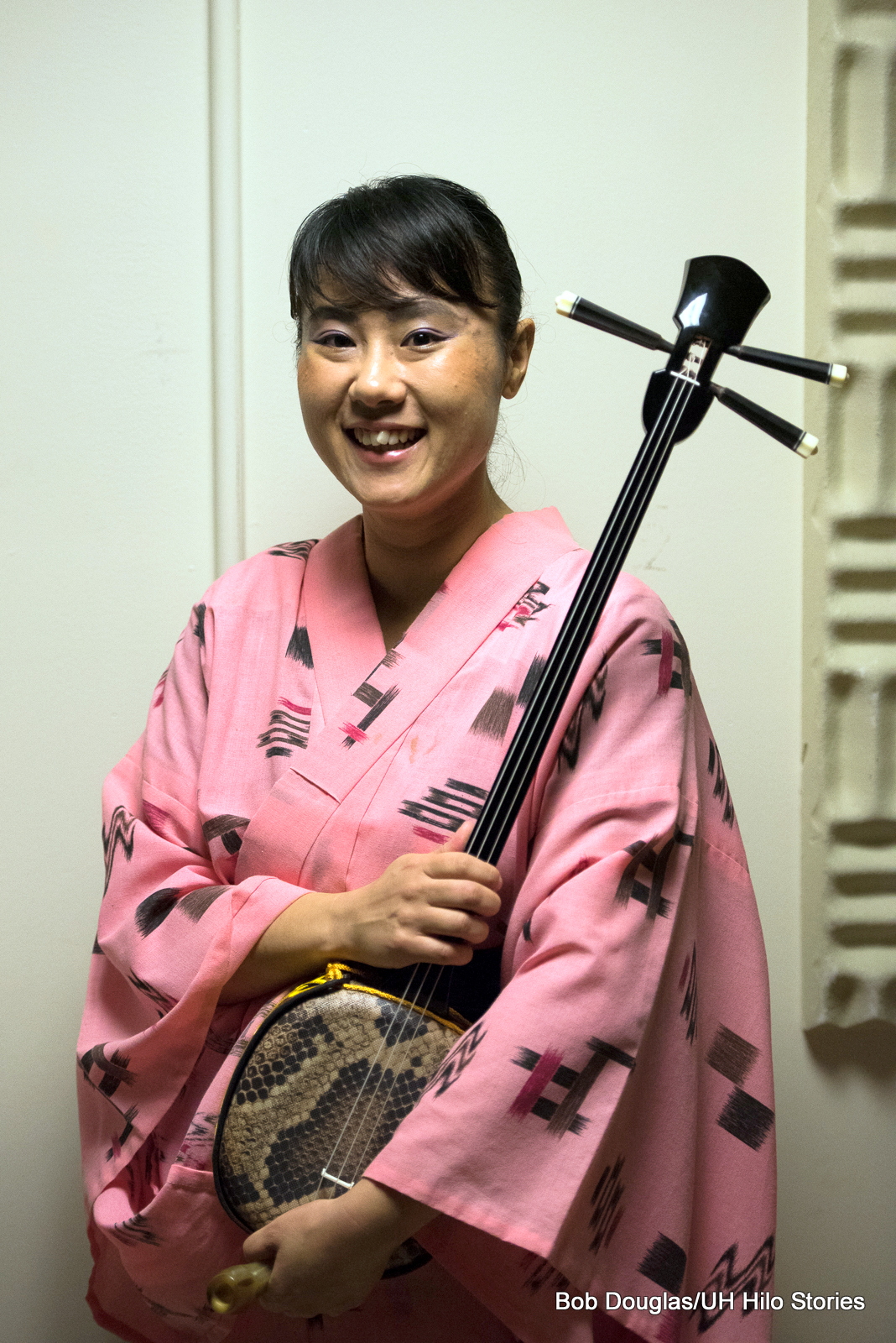Woman in traditional attire and holding stringed instrument.