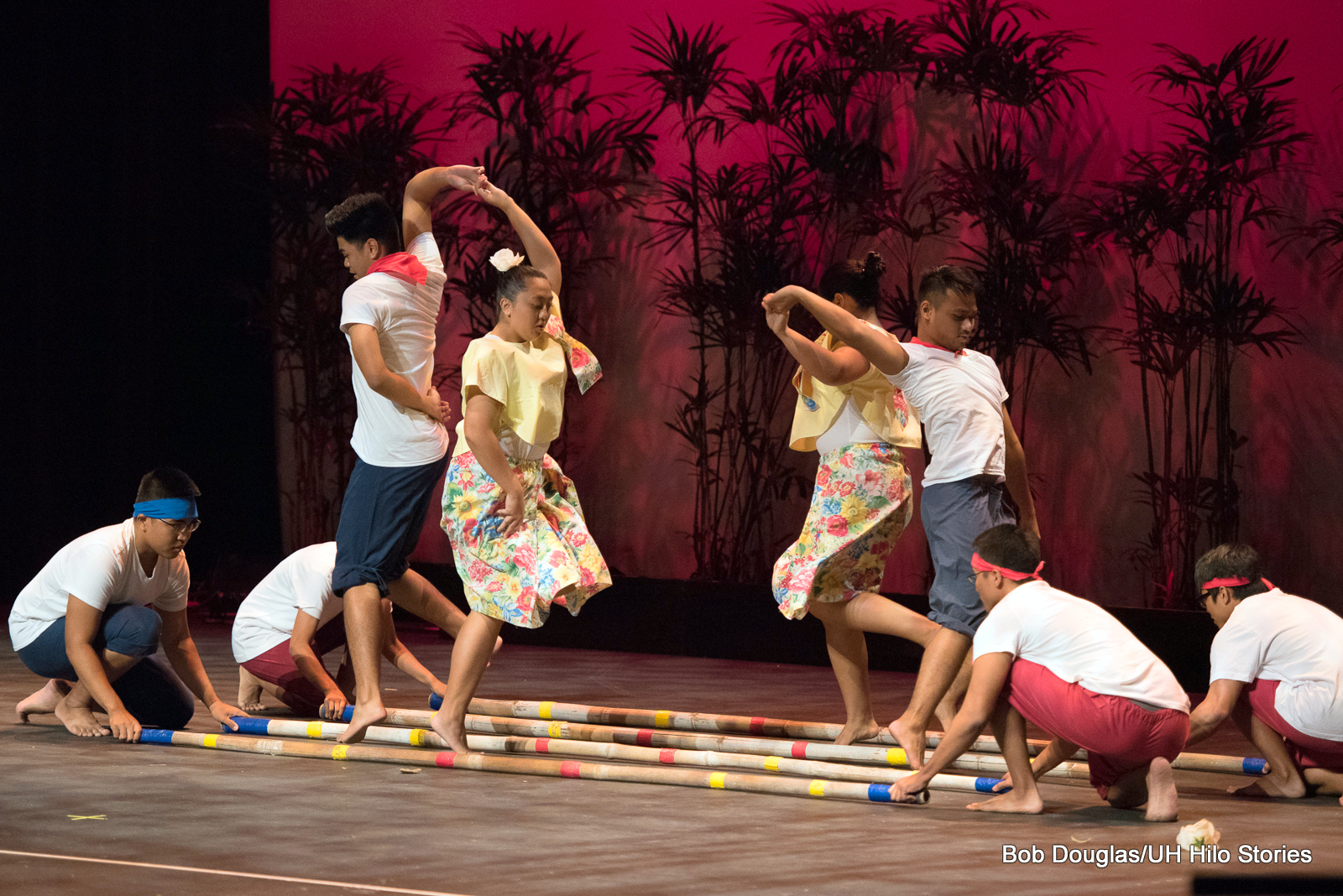 Group doing tinikling dance, men with long bamboo poles lengthwise on floor, beating rhythm while two couples dance in and out of moving bamboo.