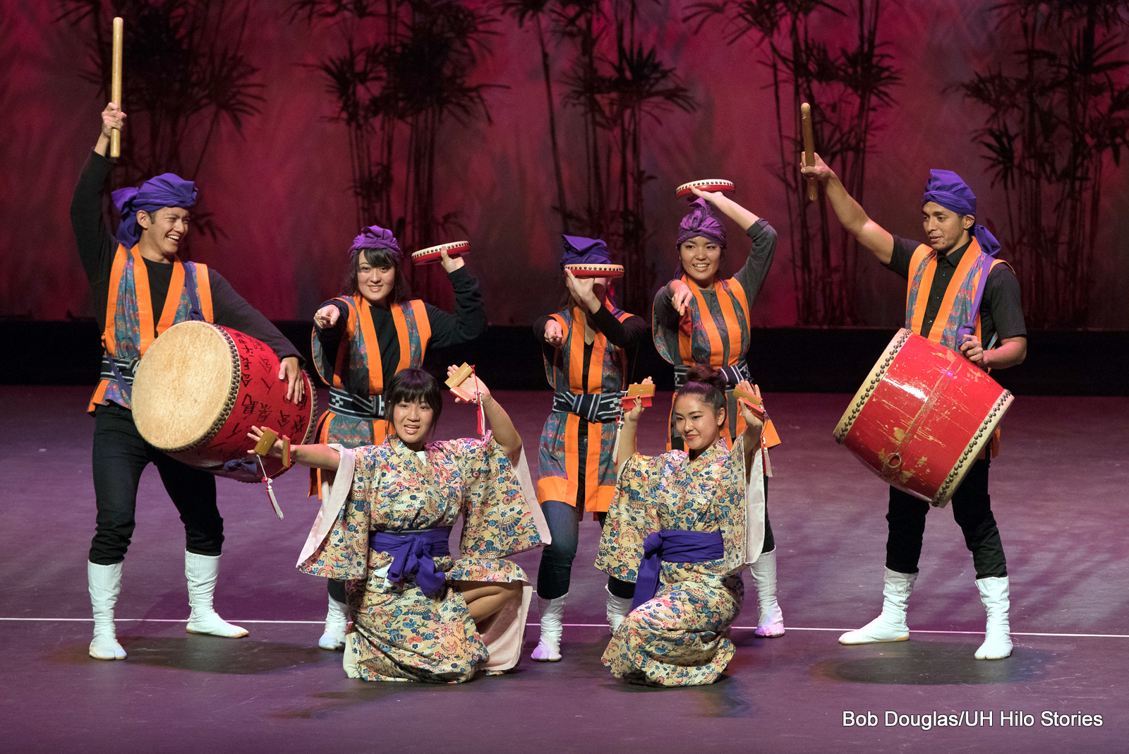 Colorful group of seven dancers in orange and purple costumes, posing just after finishing dance, each holding drums or other percussion instruments. Two women in front wearing kimono with purple sash.