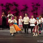 "Group of nine women and men, holding hands in circle, spinning around. Women in colorful skirts, one in pink leggings, men in white ""poet"" shirts with black pants."
