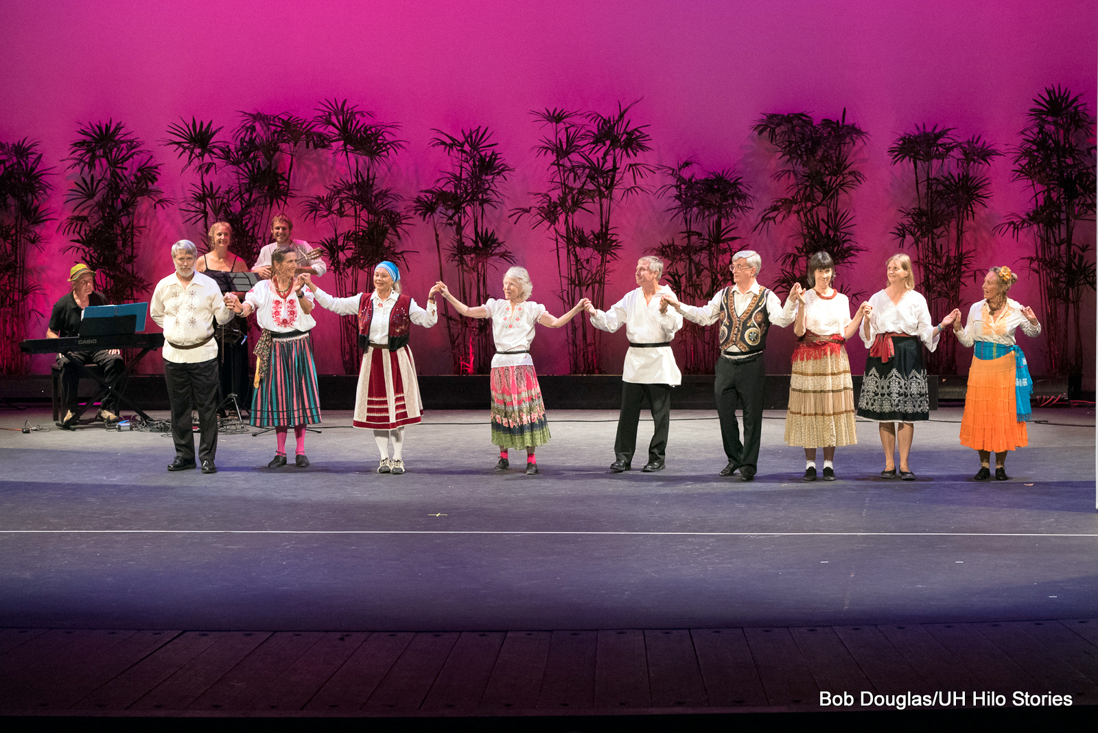 """Group of nine women and men, holding hands in circle, spinning around. Women in colorful skirts, one in pink leggings, men in white """"poet"""" shirts with black pants."""