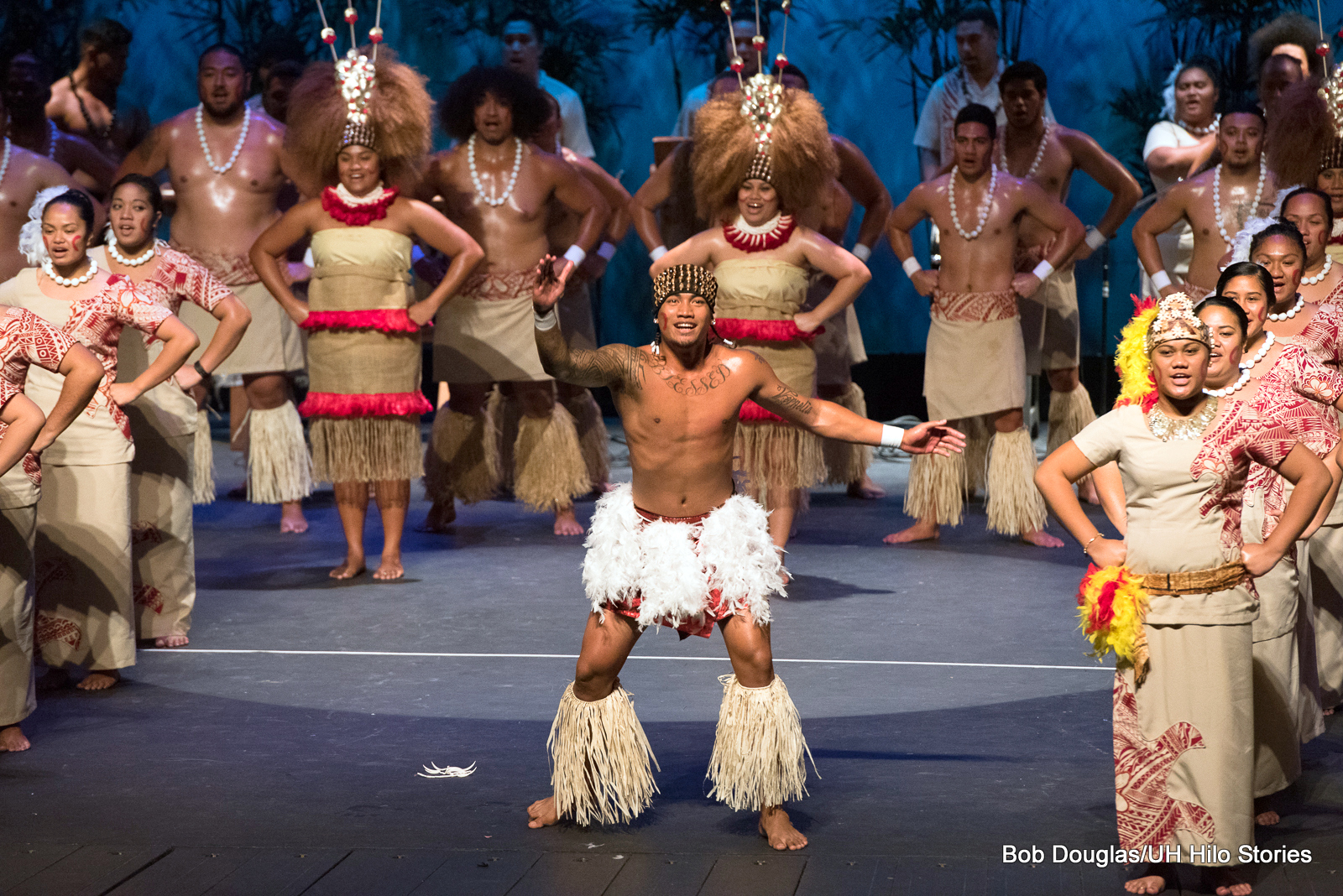 Single male dancer surrounded by group, costumes of beige and red, colorful, bold headdresses.