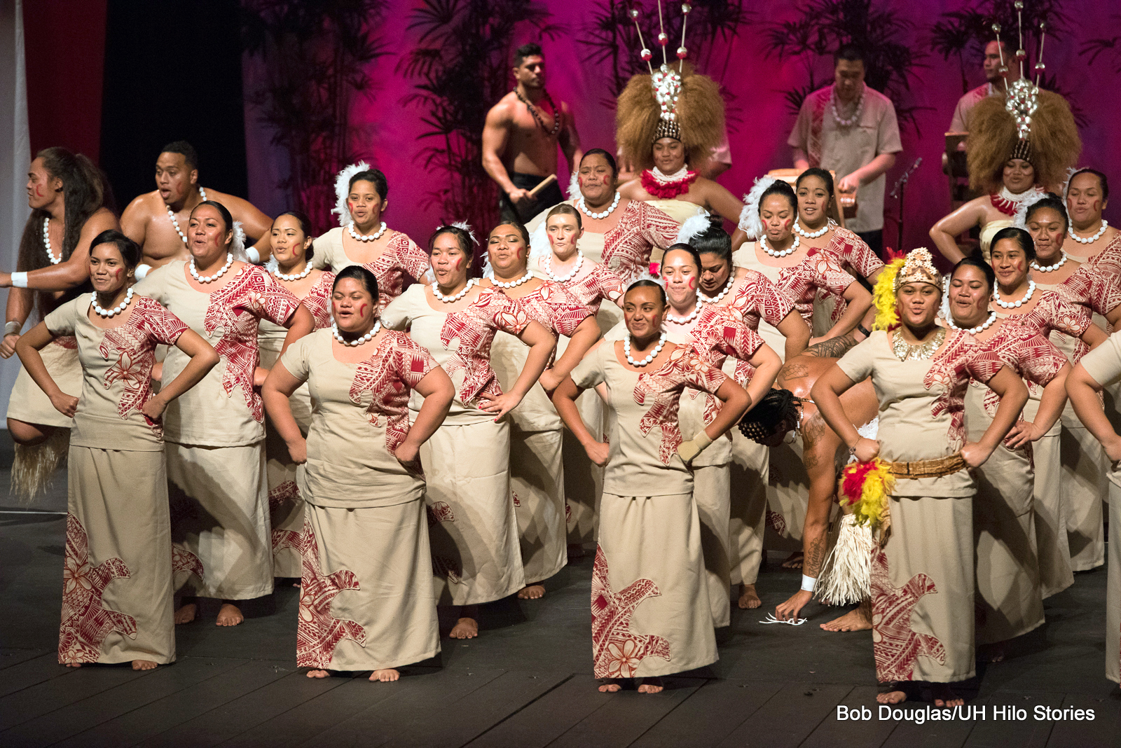 Large group of women and men, beige and red costumes, dancing.