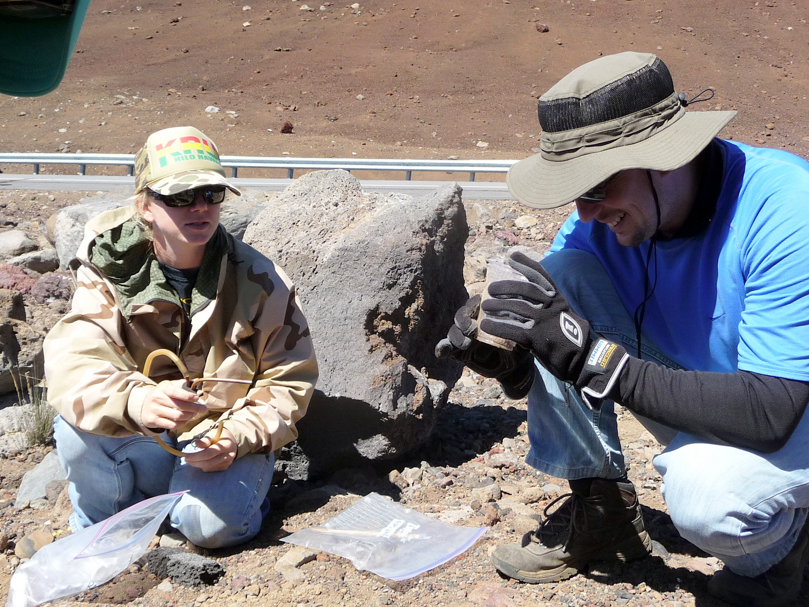 Jessica and Jesse kneeling down to collect specimens from the rocky ground.