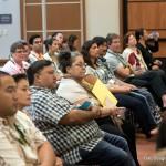 People participating in proceedings in auditorium.