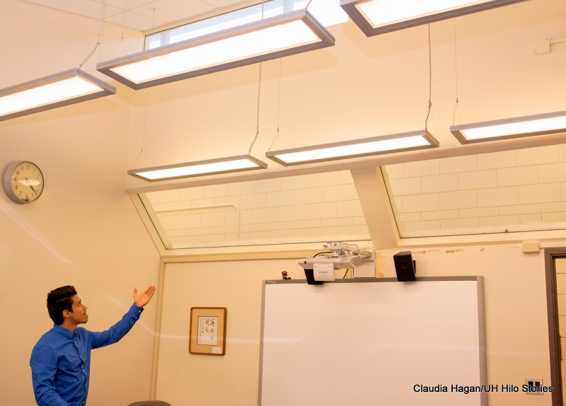 A student employee in the Office of the Chancellor points up to new light fixtures.