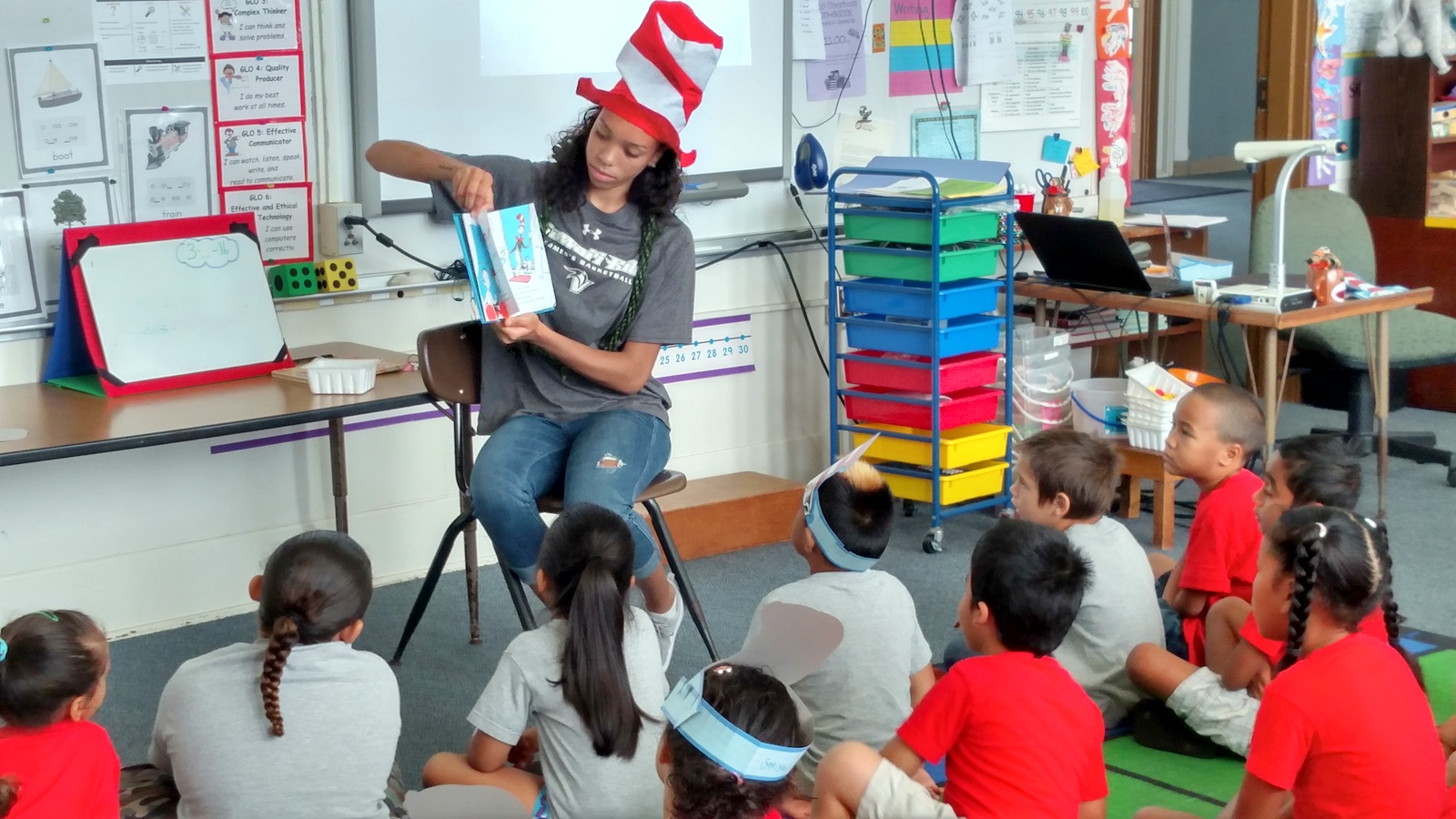 Basketball Vulcan Alia Alvarez wears a Dr. Seuss striped top hat and reads to school children gathered around her.
