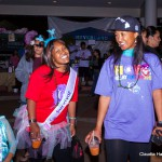 """Two female students in colorful Ts and hats, with a school girl also dressed colorfully. One of the students has a sash on that says, """"Survivor."""""""