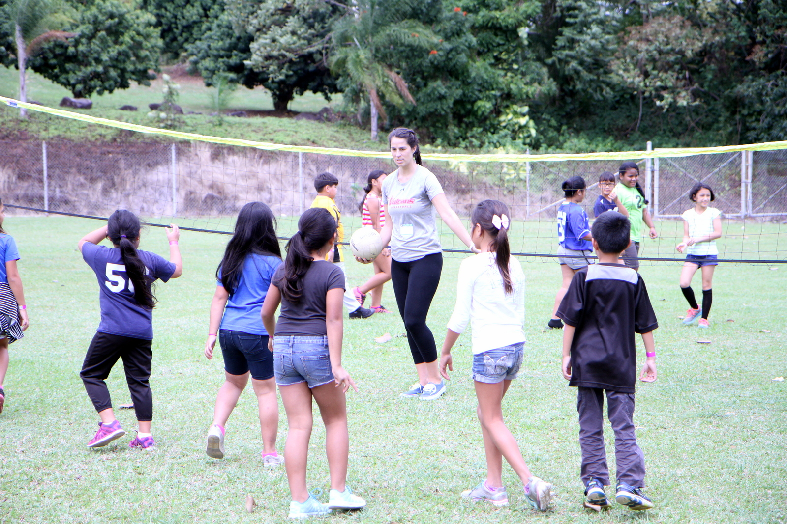 Mariya Heidenrich with school children, volleyball net with lawn court, giving instruction.