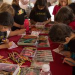 School children doing crafts at a table.