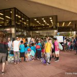 School children and their teachers gather on the Library Lanai at Earth Day booths.