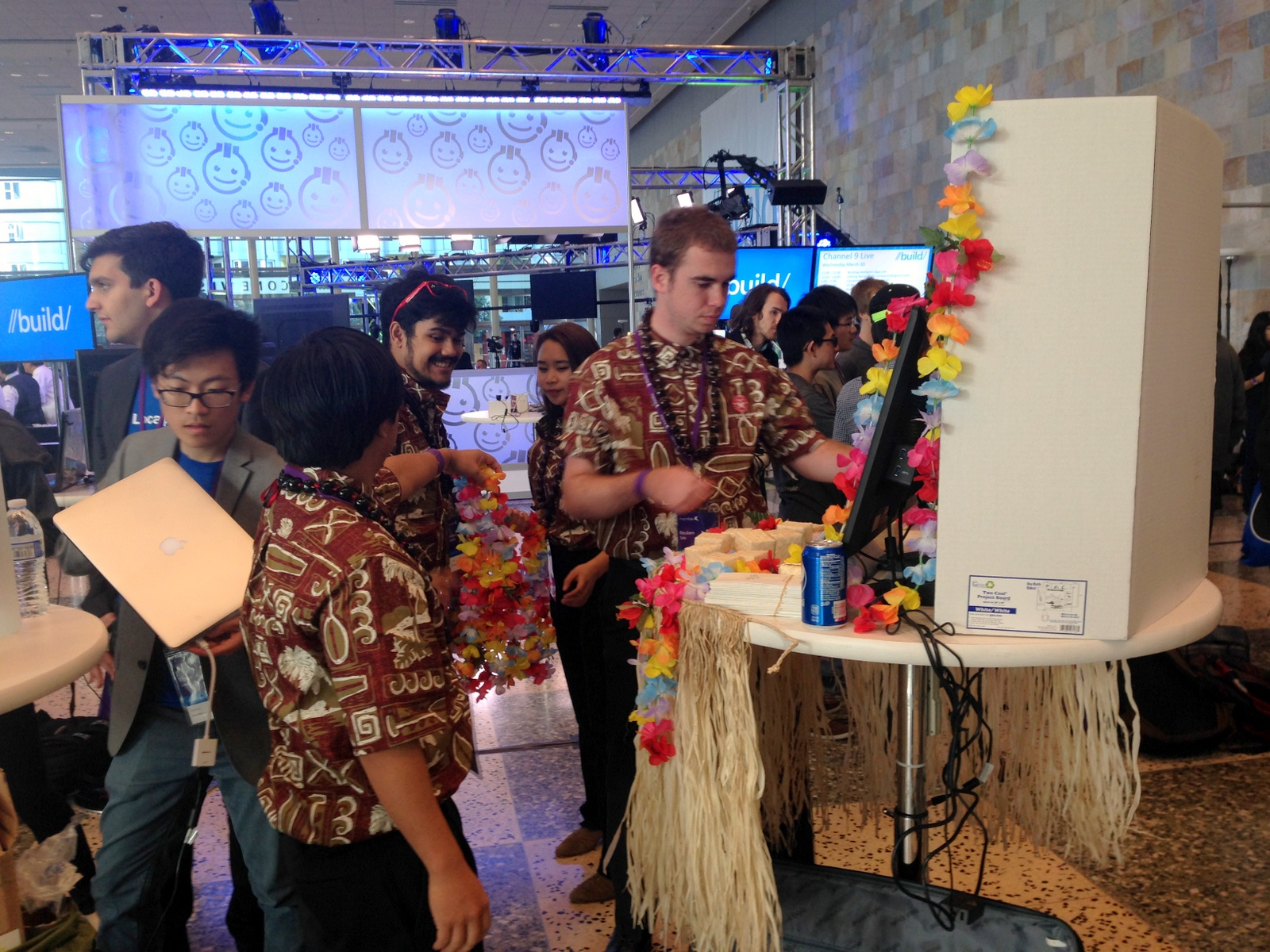The team at their booth in their matching aloha shirts. Their display has a hula skirt hanging from around the table edge and lei decorate the computer screen.