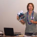 Presenter holding up a book.
