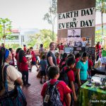 """School children and their teachers gather on the Library Lanai at Earth Day booths. In the back is a large sign, """"EARTH DAY IS EVERY DAY."""""""