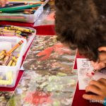 School child doing crafts with crayons and paper.