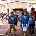 School children with identical blue tshirts walking together near the plaza.
