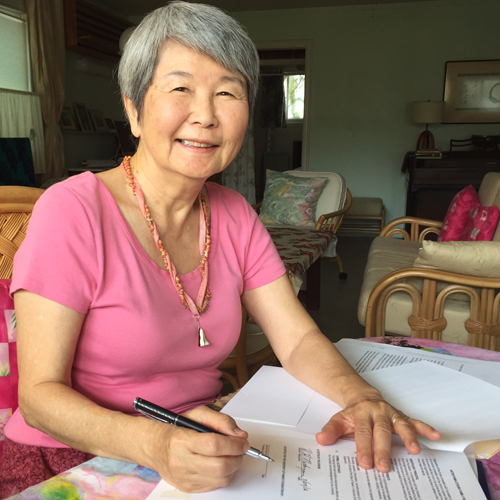 Harriet Natsuyama seated at a table, signing agreement.