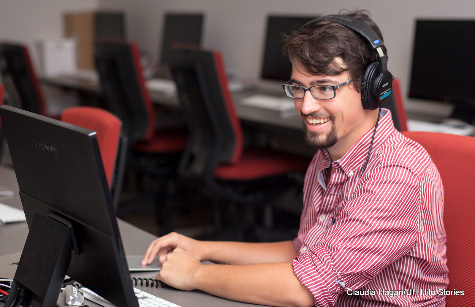 Justin Kalaniali'i Stoleson at computer with headphones on.
