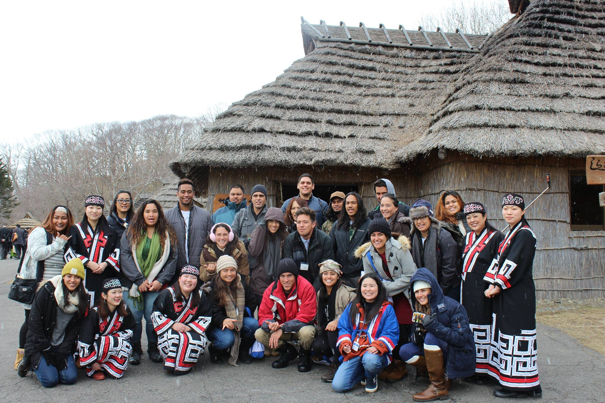 Tomodachi Scholars gathered for group photo in front of indigenous structure.