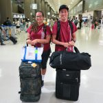 Two students with luggage in airport.