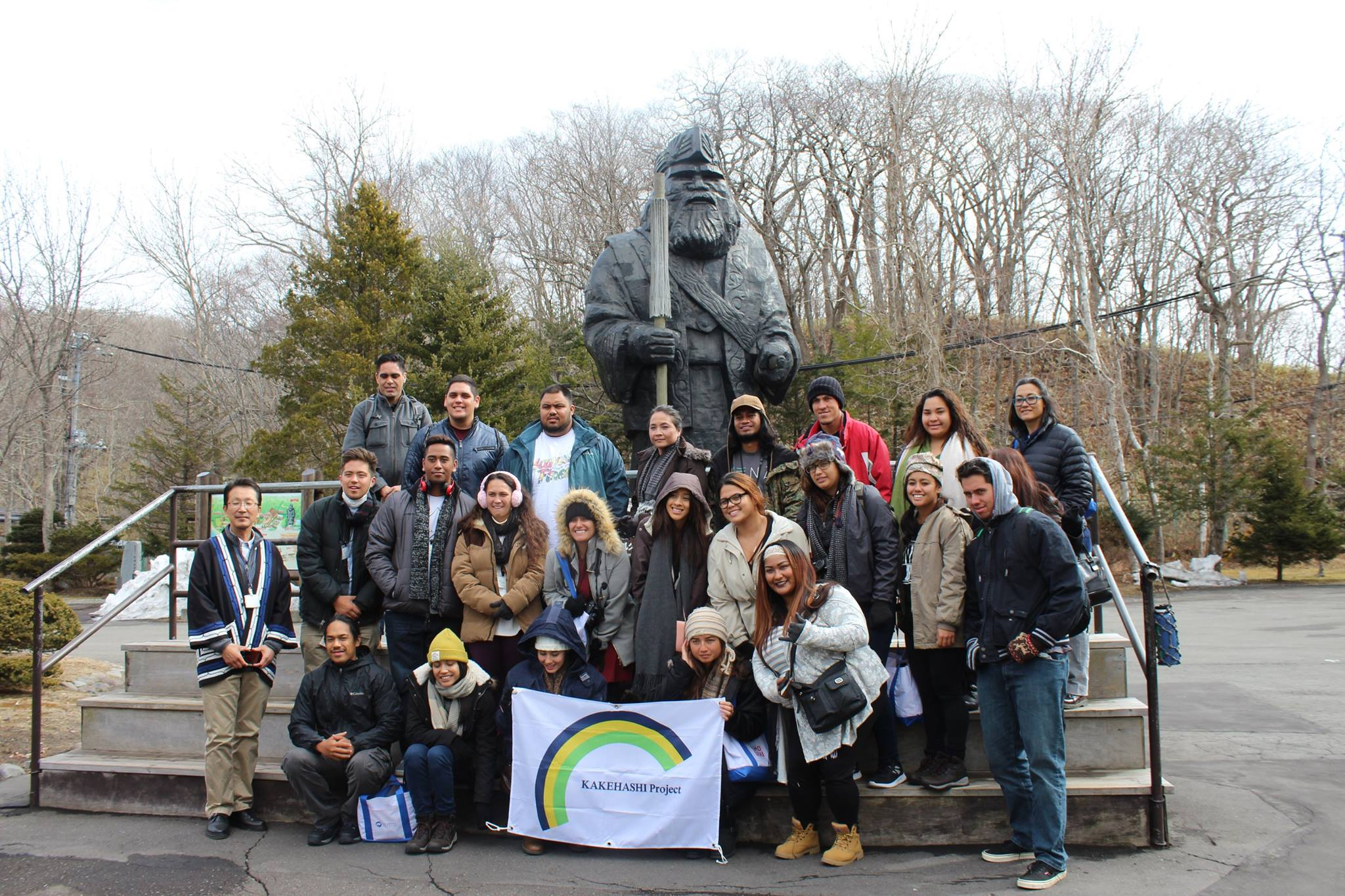 Group photo with a statue in background.