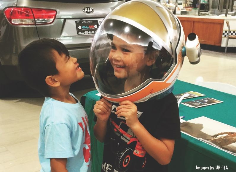 Young girl with replica of austronaut helmet on her head, smiling.