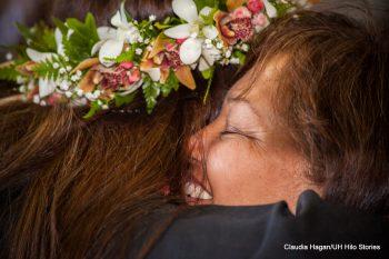 Gradute hugging family member.