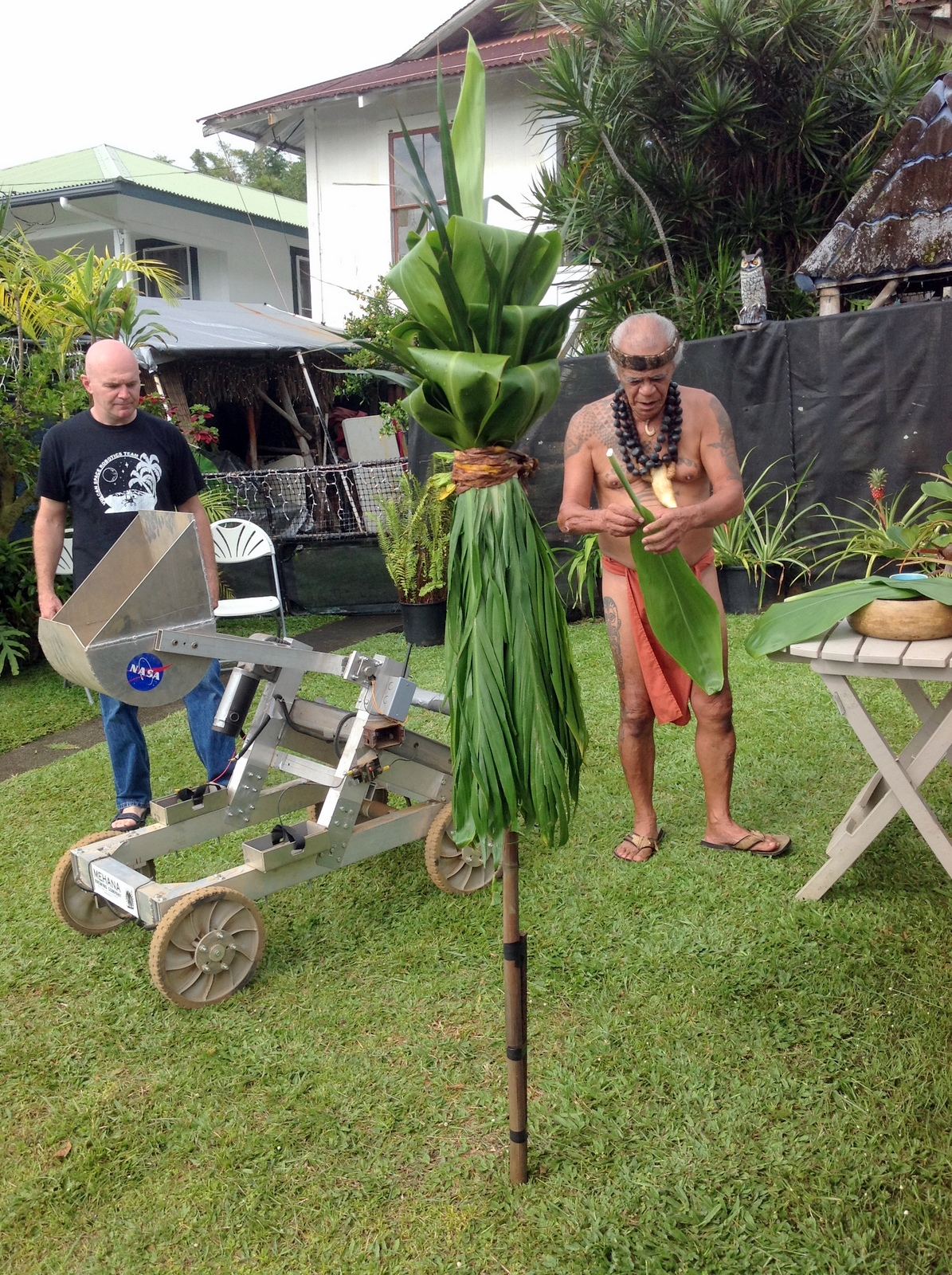 Kahuna doing blessing with ti. Robot on lawn. Marc Roberts in background.