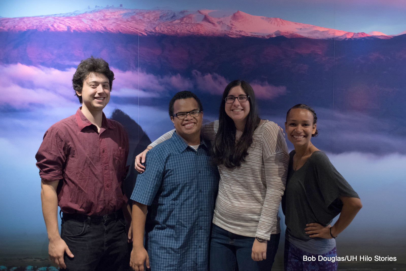 Group of four students standing for photo in front of large screen shot of Maunakea.
