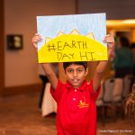 """Boy holding up sign """"#Earth Day HI"""""""