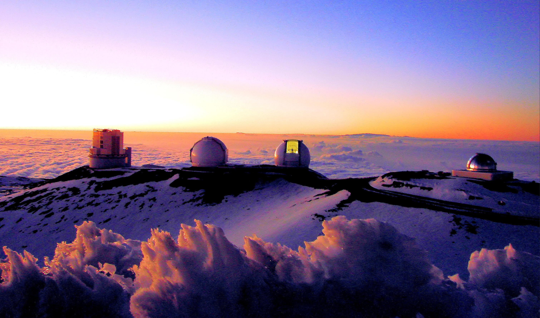 Maunakea observatories on summit, snowcovered, sunset.
