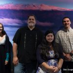 Group stands in front of screen shot of Maunakea.