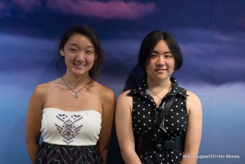 Two female students pose for photo in from of screenshot of Maunakea.