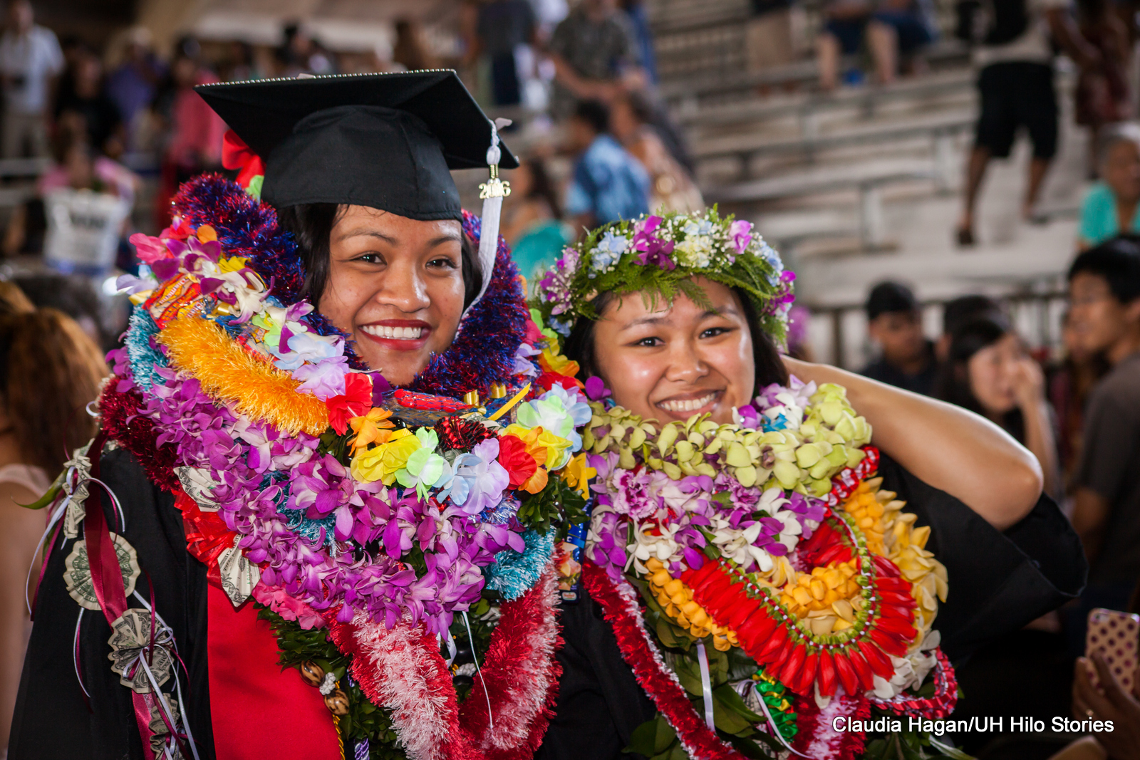 Two female graduates in regalia, smiling, one in mortarboard, one with head lei, laden with lei.