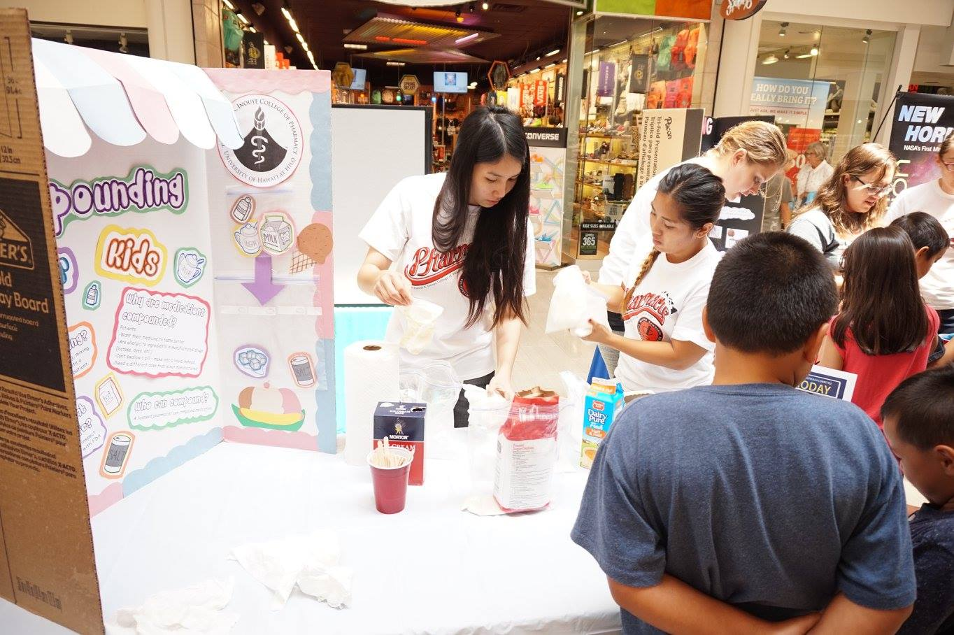 Volunteers Kaylee Hoang and Theresa Thu Nguyen show school children compounding materials.