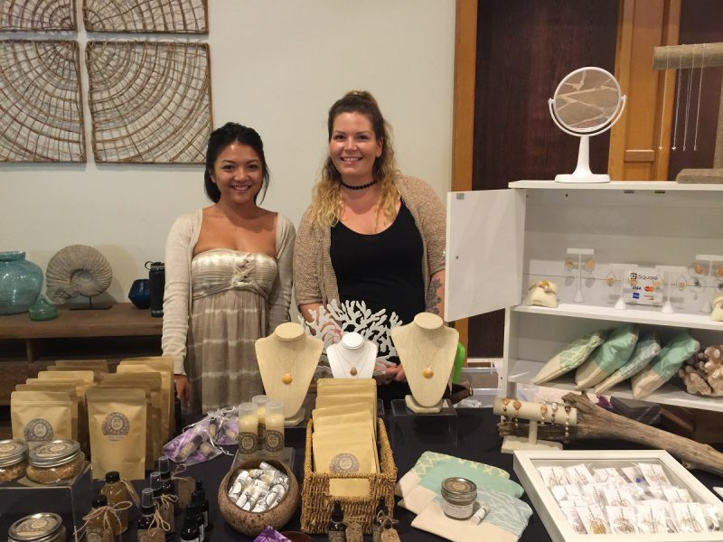 Two vendors at their table showing wares.