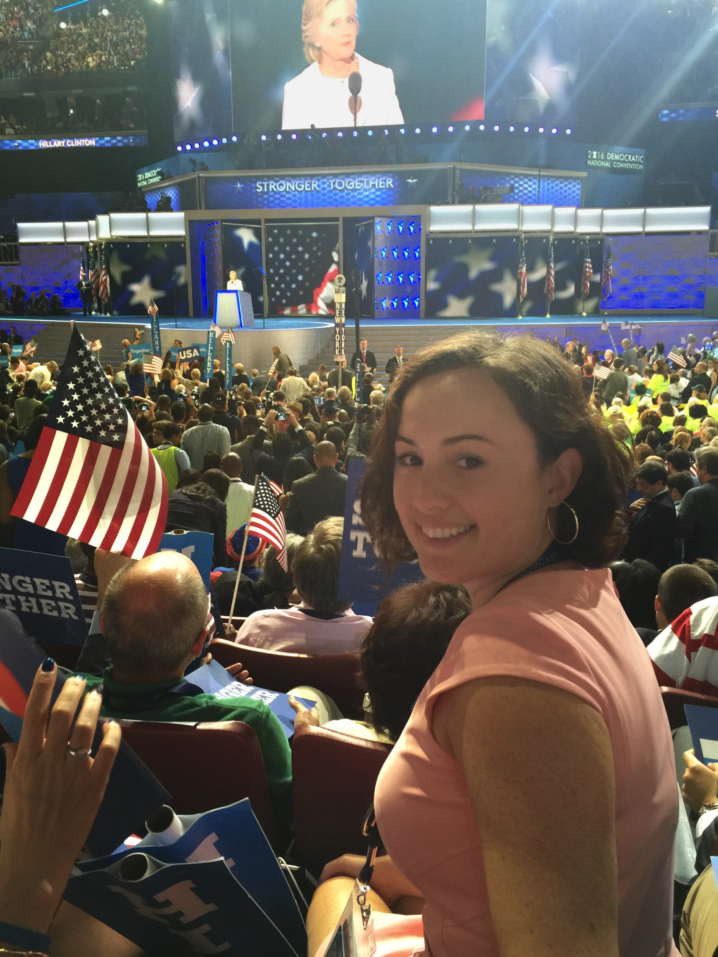 Lara Hughes on the convention floor, turned to the camera with Hillary Clinton on the stage and on the big screen in the background.