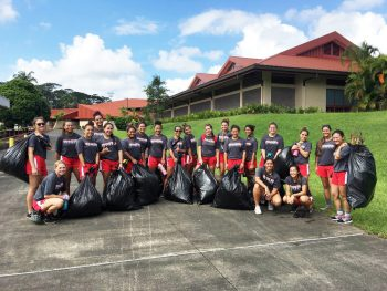 Team photo with garbage bags full.